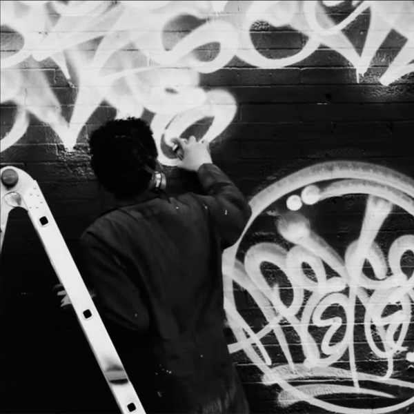 Apexer completing the Black Scale Mural on Haight Street