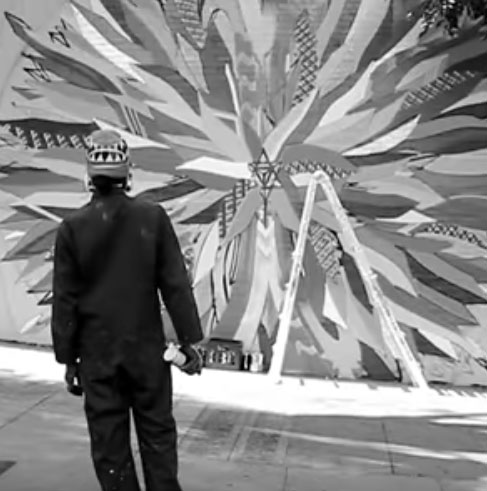 Apexer looking at unfinishedstreet art mural on Haight Street