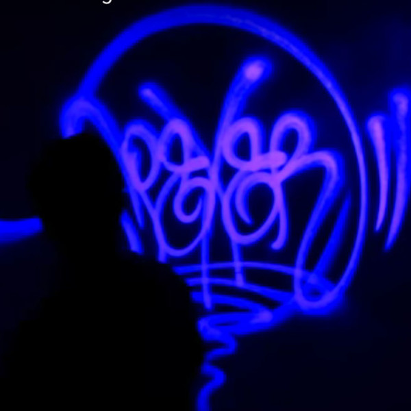 Apexer creating handstyle lettering with black light paint, San Francisco