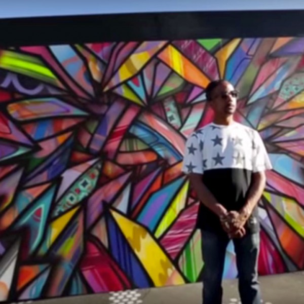 Apexer standing in front of his Adobe #CreateNow mural, San Francisco